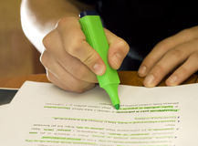 Student using marker to mark important text. Hands of a student using a green marker on school/university notes. Lit with three Speedlites: two bulbed ambient royalty free stock photos