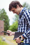 Student using mobile phone in campus. Smiling student using mobile phone in college campus Royalty Free Stock Images