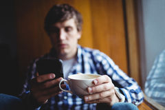 Student using mobile phone while having coffee. In college Stock Photos