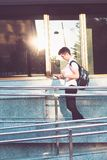 Student with the books walking at the front of university. Student using mobile phone holding a notebook and carrying a backpack walking at the front of Royalty Free Stock Photo
