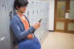 Student using mobile phone in locker room Stock Photo