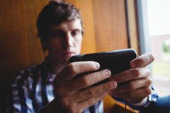 Student using mobile phone near window. In college Stock Images