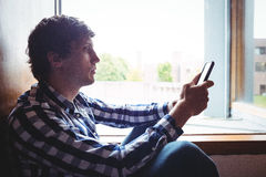 Student using mobile phone near window. In college Stock Photography