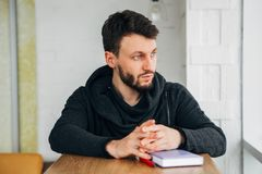 A freelancer writes a note in a notebook and looks out the window. Student using notebook at college.a male freelancer writes a note in a notebook on a wooden Royalty Free Stock Image
