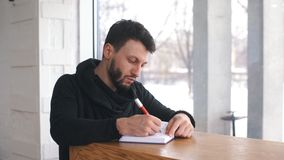 Student using notebook at college. A male freelancer writes a note in a notebook on a wooden table stock footage