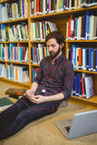 Student using phone in library on floor. At the university Royalty Free Stock Images
