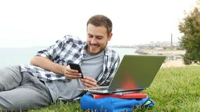 Student using smart phone lying on the grass stock footage