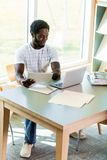 Student Using Studying In Library. Full length of male university student using digital tablet and laptop while studying in library Royalty Free Stock Photography