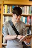 A student using a tablet computer. Portrait of a young student using a tablet computer in the library Royalty Free Stock Image