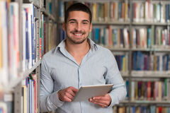 Student Using A Tablet Computer In A Library. In The Library - Handsome Male Student With Laptop And Books Working In A High School - University Library Stock Photo
