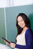 Student using tablet-pc in classroom. Smiling female student using tablet-pc in classroom Royalty Free Stock Image