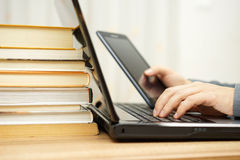 Student is using tablet pc , laptop computer and courseware at t Royalty Free Stock Image