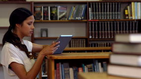 Student using tablet pc in library. In ultra hd format stock footage