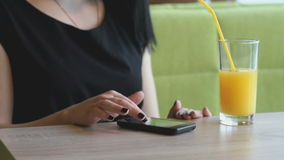 Student viewing photos using a black smartphone. Stylish student girl aged 20s viewing photos using a black smartphone at the restaurant stock footage
