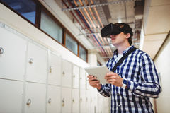 Student in virtual reality headset using digital tablet in locker room. At college Stock Photography
