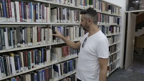Student walk into library and choose books stock video footage