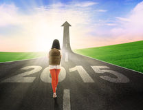 Student walk to chase her goal. Female student carrying backpack and walk on the road with upward arrow and number 2015 Stock Photo