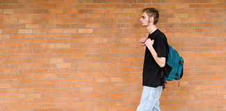 Student walking besides brick wall. A tall white Caucasian young adult teenage male walks in front of a brick wall. Lots of room for your copyspace text. He has Royalty Free Stock Photo