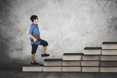 Student walking on books stair with book. Image of cute student walking on books stair while holding a textbook, concept study hard Stock Photography