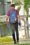Student Walking On Campus met Rugzak stock afbeeldingen