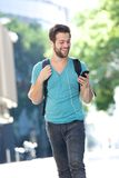 Student walking on campus with mobile phone. Portrait of a happy male student walking on campus with mobile phone Royalty Free Stock Image
