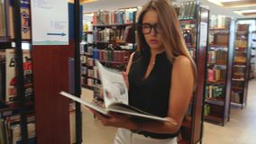 Student walking through the library and reads the encyclopedia stock video