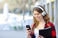 Student walking listening to music checking phone royalty free stock photography