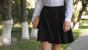 A student walks down the street with textbooks in her hands in the summer park. schoolgirl in the city. girl teenager