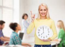 Student with wall clock and finger up Stock Images