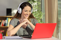 Student watching video tutorials on line. Portrait of a beautiful student viewing and listening video tutorials on line with headphones and a red pc sitting in a royalty free stock photos