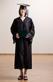 Student wearing cap and gown holding diploma Stock Photos