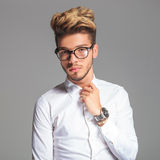 Student wearing glasses while posing and fixing his shirt Stock Photos