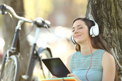 Student wearing headphones listening to music on line. Single student wearing headphones listening to music on line with a tablet outdoors in a park Royalty Free Stock Photos