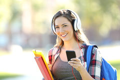 Student wearing headphones looking at you. Beautiful student wearing headphones listening music and looking at you in the street Royalty Free Stock Image