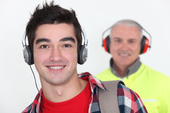 Student wearing headphones near builder Stock Photography