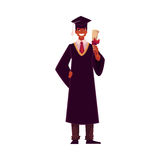 Student wearing traditional graduation gown and cap, holding diploma Royalty Free Stock Photography