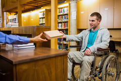 Student in wheelchair at the library counter Royalty Free Stock Photo
