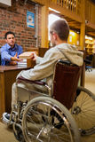 Student in wheelchair at the library counter Royalty Free Stock Photos