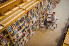 Student in wheelchair picking a book from shelf Royalty Free Stock Image
