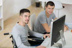 Student in wheelchair typing on laptop in classroom. Student in wheelchair typing on his laptop in classroom Royalty Free Stock Photos