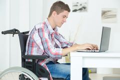 Student in wheelchair typing on laptop in library. Student in wheelchair typing on his laptop in library stock photos