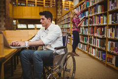 Student in wheelchair typing on his laptop while woman searching books. Student in wheelchair typing on his laptop while women searching books in library Royalty Free Stock Photo