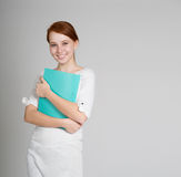 Student in white dress with green folder looking to the camera Royalty Free Stock Image