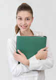 Student in white shirt with green folder looking to the camera. Gray background Royalty Free Stock Image