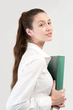 Student in white shirt with green folder looking to the camera. Gray background Royalty Free Stock Photography