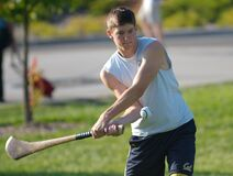 Student in white shirt practicing hurling hitting ball 2 Royalty Free Stock Photos