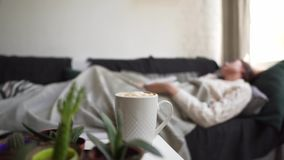 A student in a white sweater fell asleep on the couch, studying a book. Girl on the background of a cup of hot coffee. 4k stock footage