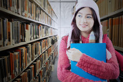 Student with winter clothes in library aisle Royalty Free Stock Images