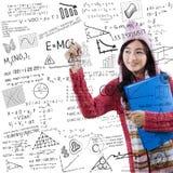 Student in winter clothes writes formula math. Joyful female student wearing sweater and hat, writing formula math on the whiteboard Royalty Free Stock Photo