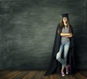 Student Woman över svart tavlabakgrund, skolaflickaakademikermössa royaltyfri fotografi